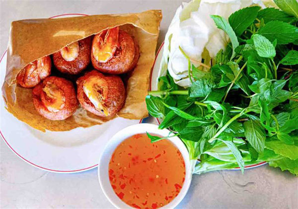 Fried shrimp cakes are served with lettuce, herbs and sweet and sour fish sauce. (Photo: Vietnamnet)
