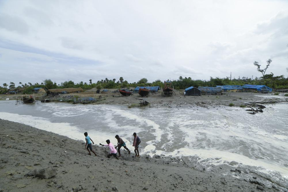 Village men walk past as sea water gushes in after breaking an embankment on the Bay of Bengal coast in South 24 parganas, West Bengal state, India, Tuesday, May 25, 2021. Tens of thousands of people are evacuating low-lying areas as Cyclone Yaas is expected to make landfall early Wednesday in Odisha and West Bengal states. (AP Photo/Mehaboob Uddin Gazi)