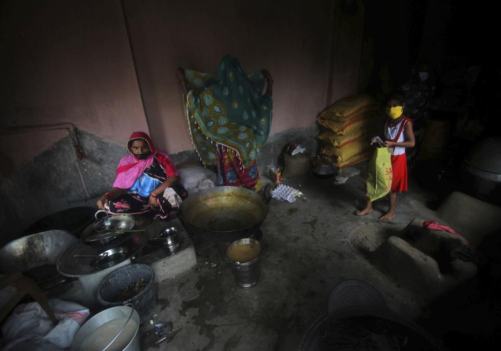 Village women who have taken refuge at a cyclone shelter prepare a meal in Balasore district in Odisha, India, Tuesday, May 25, 2021. Tens of thousands of people were evacuated Tuesday in low-lying areas of two Indian states and moved to cyclone shelters to escape a powerful storm barreling toward the eastern coast. (AP Photo)