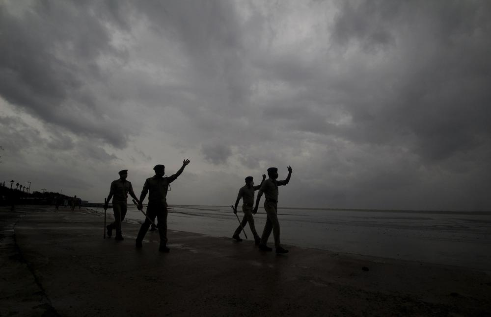Policemen ask people to move to cyclone shelters as they patrol a beach in Balasore district in Odisha, India, Tuesday, May 25, 2021. Tens of thousands of people were evacuated Tuesday in low-lying areas of two Indian states and moved to cyclone shelters to escape a powerful storm barreling toward the eastern coast. (AP Photo)