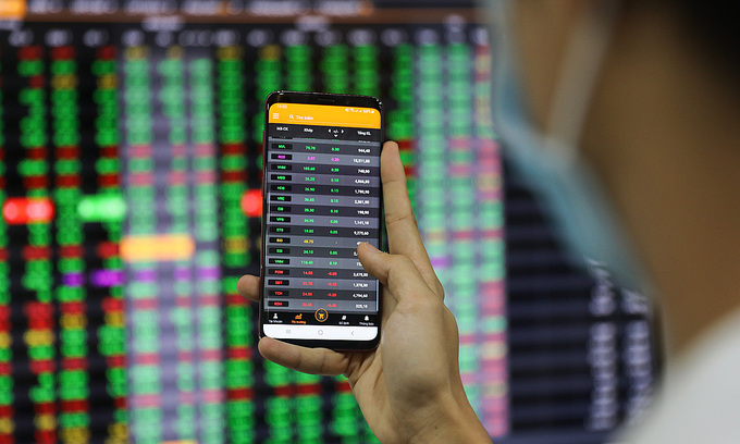 An investor looks at stock prices on a smartphone at a brokerage in HCMC's District 1, January 2020. Photo by VnExpress/Quynh Tran