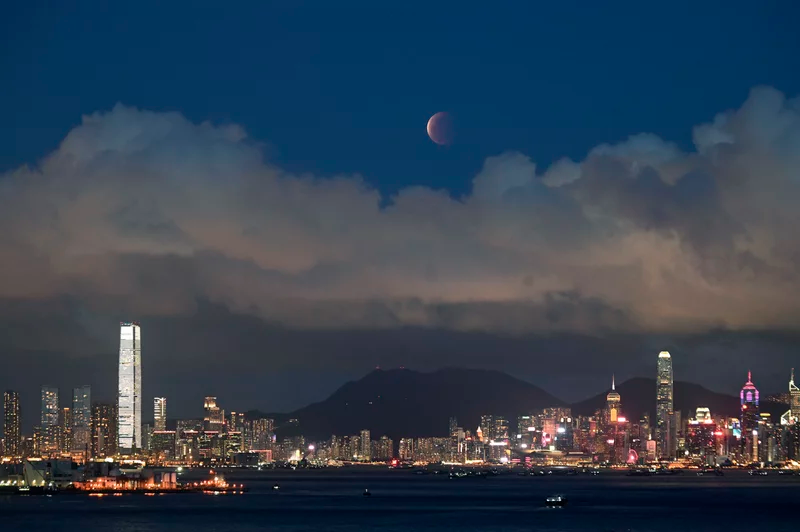 The moon rises over Victoria Harbour in Hong Kong on Wednesday. Kin Cheung/AP