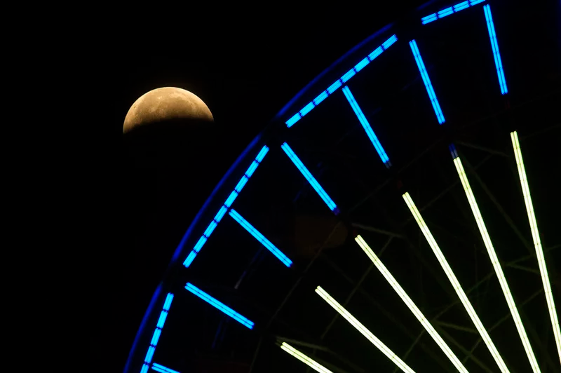 The lunar eclipse progresses behind a Ferris wheel over Santa Monica Beach on Wednesday in Santa Monica, Calif. The first total lunar eclipse in more than two years is coinciding with a supermoon. Ringo H.W. Chiu/AP