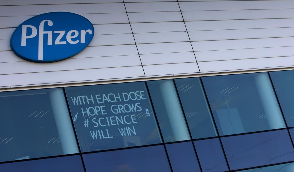 In this Tuesday, Feb. 23, 2021 file photo, a sign is pasted into an upper window at Pfizer manufacturing center in Puurs, Belgium. The European Union cemented its support for Pfizer-BioNTech and its novel COVID-19 vaccine technology, Saturday, May 8, 2021 by agreeing to a massive contract extension for a potential 1.8 billion doses through 2023.