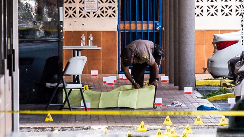 A Miami-Dade officer covers a body outside a club that was rented out for a concert. (Photo: CNN)
