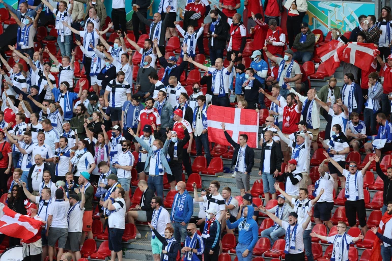 Finland and Denmark fans cheer the name of Denmark's Christian Eriksen inside the stadium after the match is postponed [Wolfgang Rattay/Reuters]