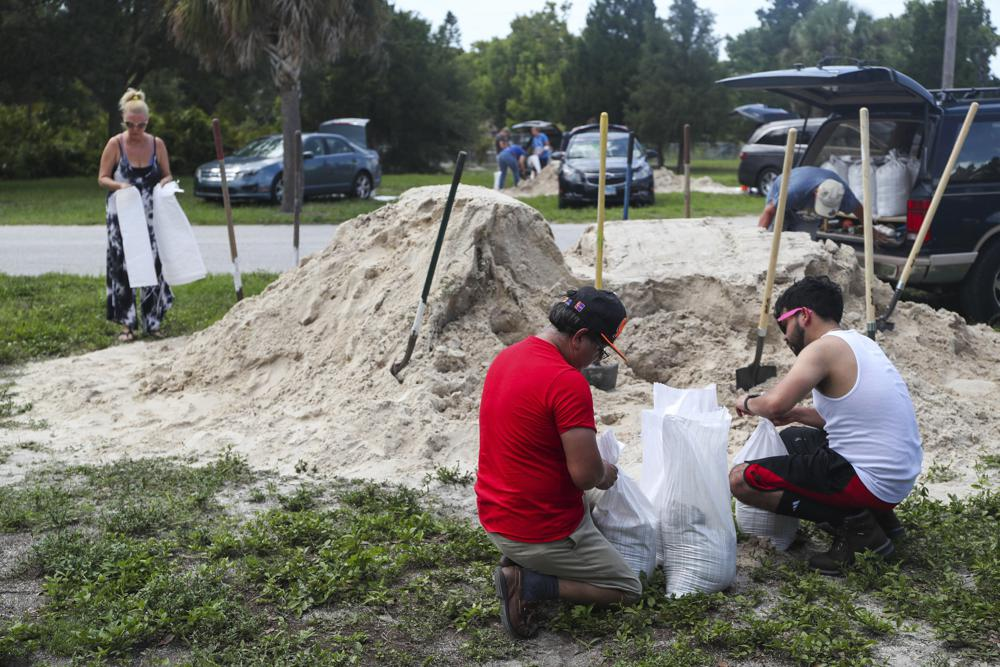 People fill sandbags to prep for storm Elsa at Walsingham Park, Monday, July 5, 2021 in Seminole, Fla. (Arielle Bader /Tampa Bay Times via AP)