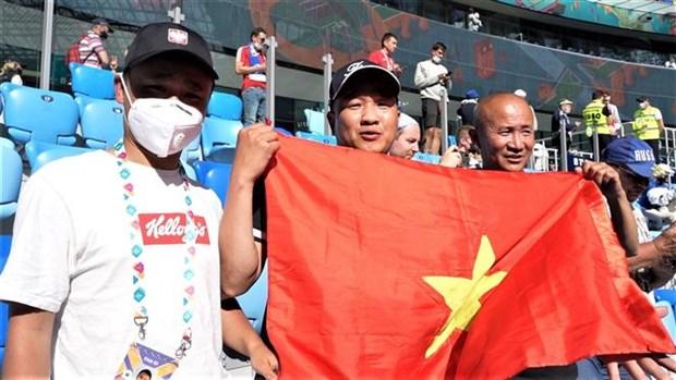 Hoang Van Phu (middle) and Nguyen Duc Vuong (right) holding Vietnam's flag at Vladivostok. Photo: VNA