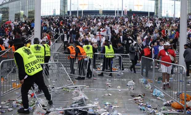 Stewards replace barricades after they were knocked over by supporters outside Wembley during the Euro 2020 final. Photograph: David Cliff/AP