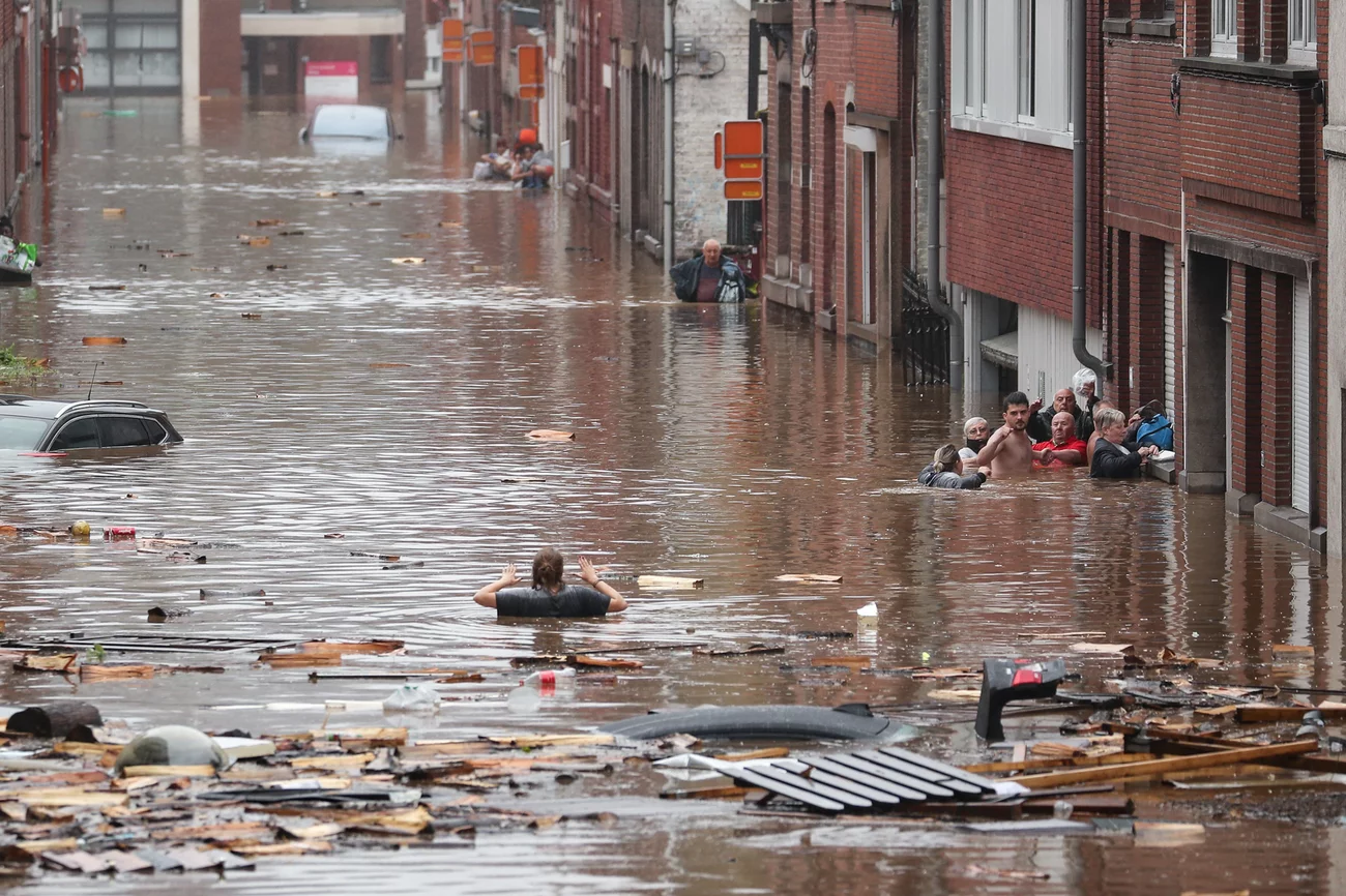 A woman tries to move in a flooded street following heavy rains Thursday in Liège, Belgium. Bruno Fahy/Belga/AFP via Getty Images