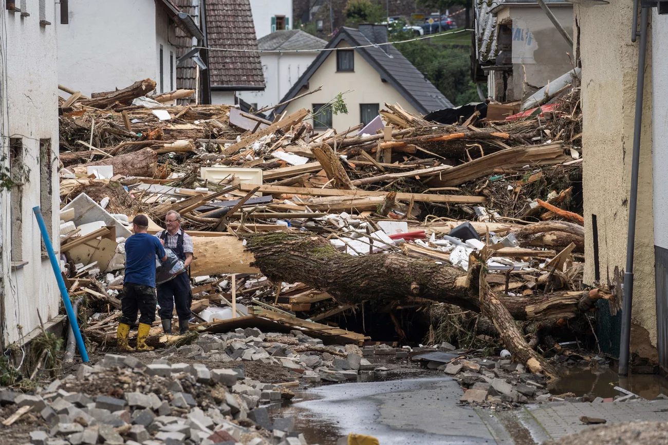 Two men try to secure goods near houses destroyed by floods Thursday in Schuld. Bernd Lauter/AFP via Getty Images