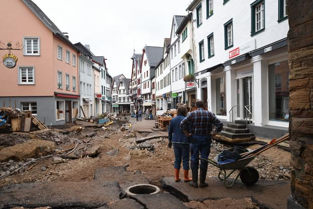A man and a woman stand with a wheelbarrow as they look at the destroyed pavement of the pedestrian zone in Bad Muenstereifel, western Germany, on July 16, 2021. INA FASSBENDER/AFP VIA GETTY IMAGES