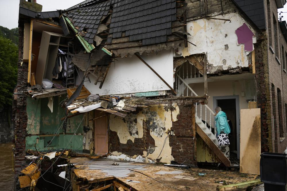 A woman walks up the stairs in her damaged house after flooding in Ensival, Vervier, Belgium, Friday July 16, 2021.  Photo: AP
