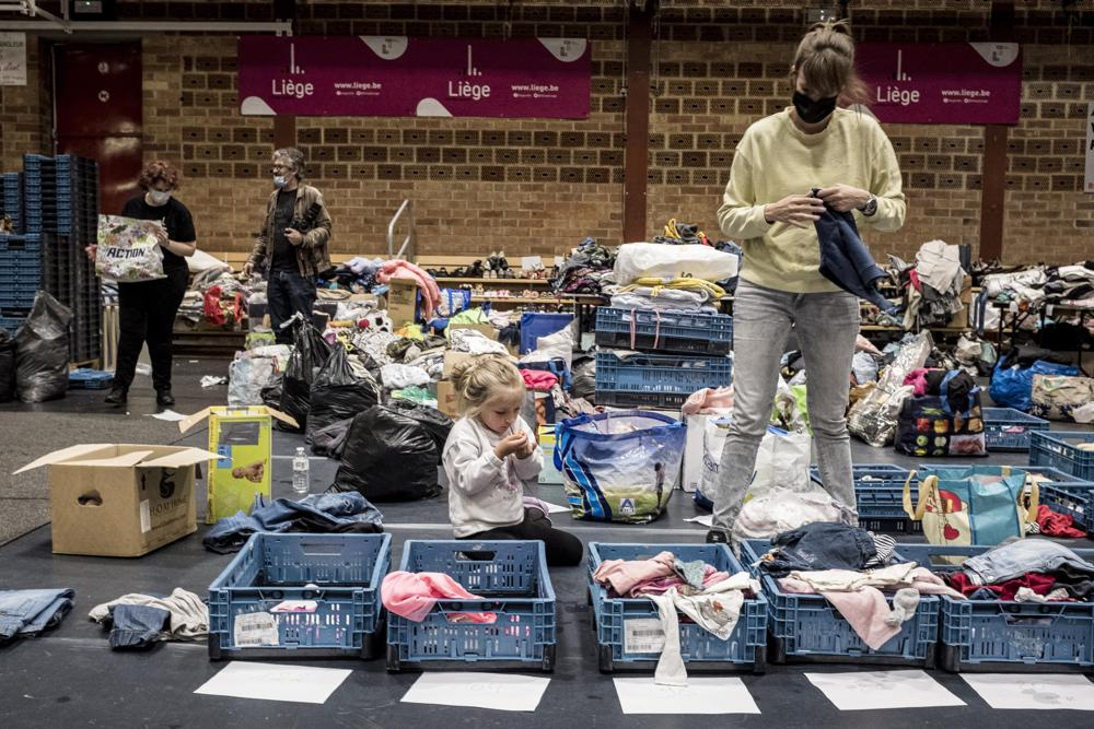 A woman sorts through clothing in a shelter for residents after flooding in Angleur, Province of Liege, Belgium, Friday July 16, 2021. Photo: AP