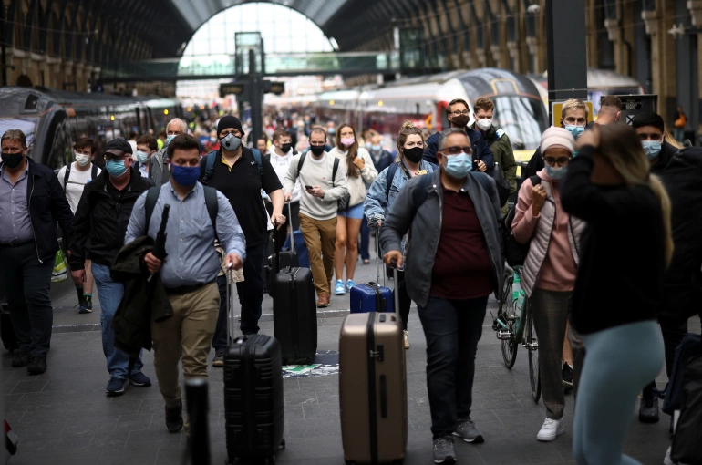 People wearing protective face masks walk along a platform at King's Cross Station, amid the coronavirus disease (COVID-19) outbreak in London [File: Henry Nicholls/Reuters]