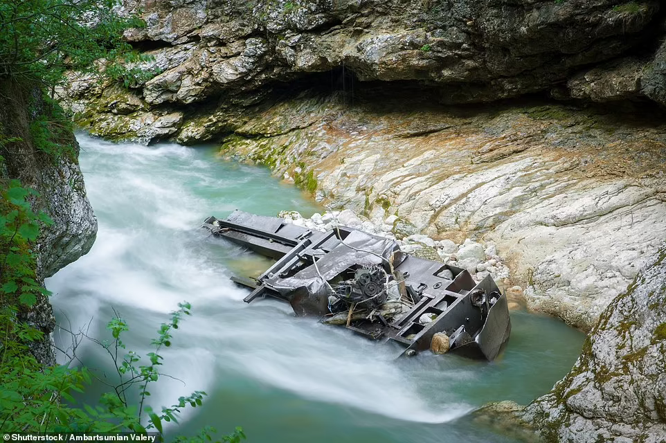 An old locomotive lies at the bottom of a mountain river close to an old narrow-gauge railway in the Guam Gorge in Adygea in the Caucasus region . Photo: Shutterstock