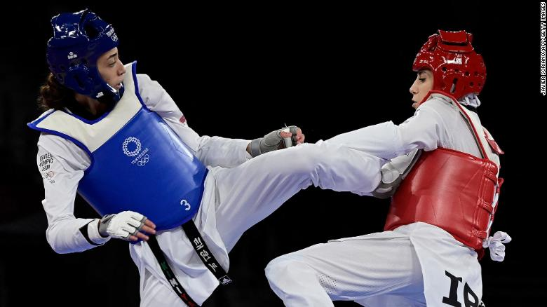 Refugee Olympic Team's Kimia Alizadeh (Blue) and Iran's Nahid Kiyani Chandeh (Red) compete in the taekwondo women's -57kg elimination round bout during the Tokyo 2020 Olympic Games at the Makuhari Messe Hall in Tokyo on July 25, 2021. Photo: CNN
