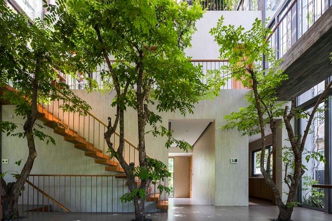 In a space created by a block that cuts through three floors, the living room blends with the greenery outside.