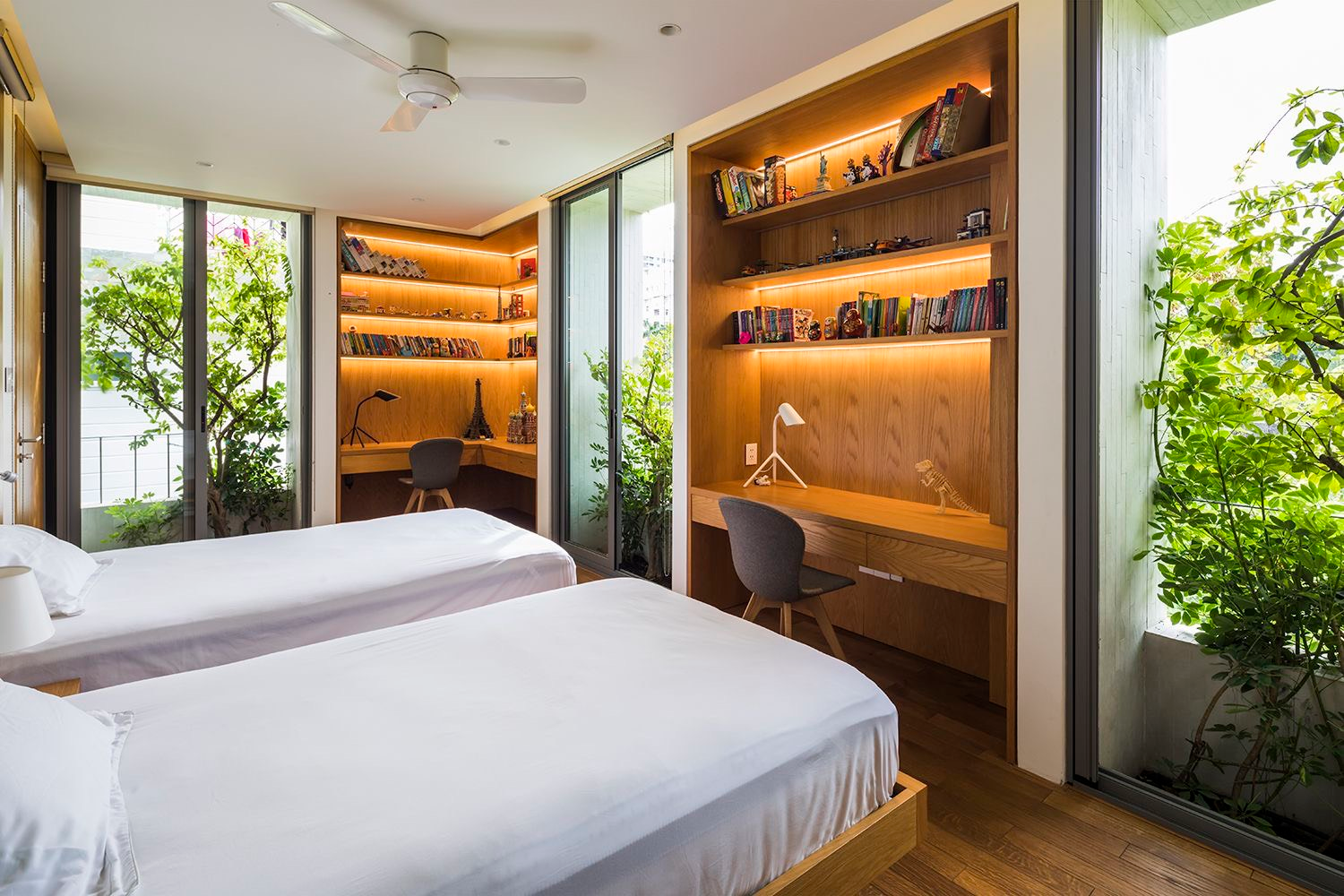 The bedrooms are greened by more than wooden shelves and the usual potted plants. Vines and trees planted just outside glass walls limit provide shade from the sun while providing plenty of natural light.