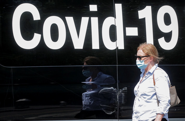 Alarms are sounding in the United States about the spreading Delta variant of the coronavirus as a woman wearing a mask passes by a COVID-19 mobile testing van in New York City on July 22 [Brendan McDermid/Reuters]
