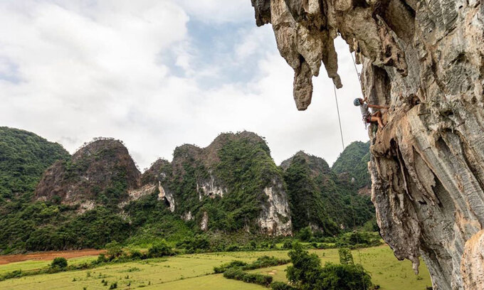 The mountain scenery at Huu Lung District, Lang Son Province. Photo courtesy of VietClimb. Intrepid travelers seeking adrenaline pumping thrill can choose to conquer virtually vertical mountain slopes in Lang Son Province. Yen Thinh Commune in Lang Son's Huu Lung District has a network of big mountains, many of them with vertical slopes. Provincial authorities are now looking to tap the commune's adventure tourism potential as a signature product, and a new rock climbing tour has been launched.  There are five main climbing spots now, with more than 110 climbing paths at many different levels. Two tours are offered every month for travelers to try and scale the tough slopes.  The price for a two-day-one-night tour is VND2.7 million ($116), and a one-day tour is VND1.3 million. The cost includes catering services, sleeping spot, climbing equipment, guide and transportation. Visitors who do not have specialized climbing shoes can rent a pair for VND100,000 a day.  The tours will have a technical assistant to help people climb to the top safely. As another safety measure, a maximum of 20 people are allowed to climb at one spot.  The rock climbing tour in Yen Thinh Commune, Lang Son Province. Photo courtesy of the Vietnam National Administration of Tourism.