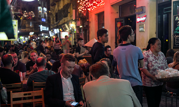 Foreign tourists sit at a beer stall in Ta Hien-Luong Ngoc Quyen intersection in Hanoi, 2019. Photo by VnExpress/Giang Huy.