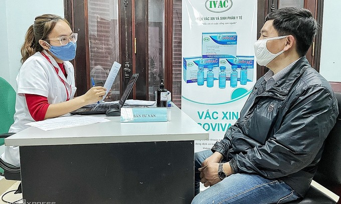 A researcher (L) informs a volunteer about the Covivac vaccine trials at the Hanoi Medical University. Photo by VnExpress