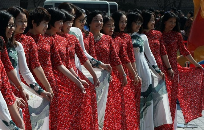 """A group of Vietnamese tourists dressed in indigenous """"ao dai"""" gowns poses for a photo in front of the presidential office in Seoul on April 3, 2019. (Yonhap)"""
