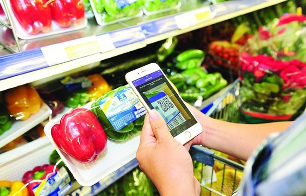 A customer uses smart phone to scan code on a product (Photo: VNA)