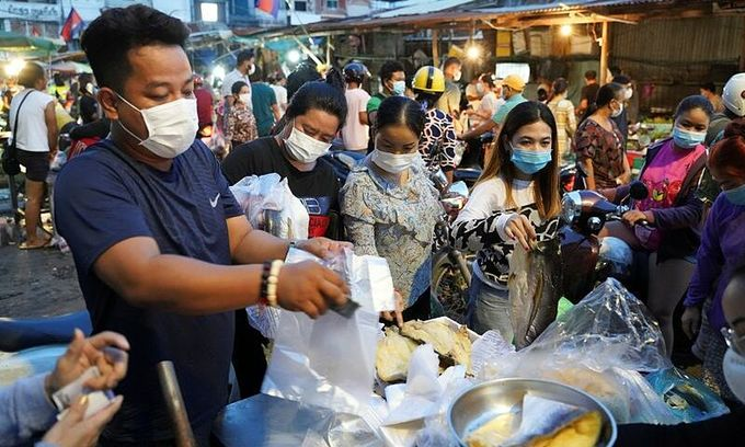 People wearing protective face masks rush to buy groceries at a fresh market amid rumors of a citywide lockdown during the latest Covid-19 outbreak at a temple in Phnom Penh, Cambodia, April 14, 2021. Photo by Reuters/Cindy Liu.
