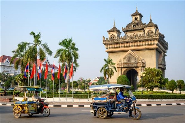 Vehicles pass through Patuxay Monument in Vientiane (Illustrative photo: AFP/VNA)