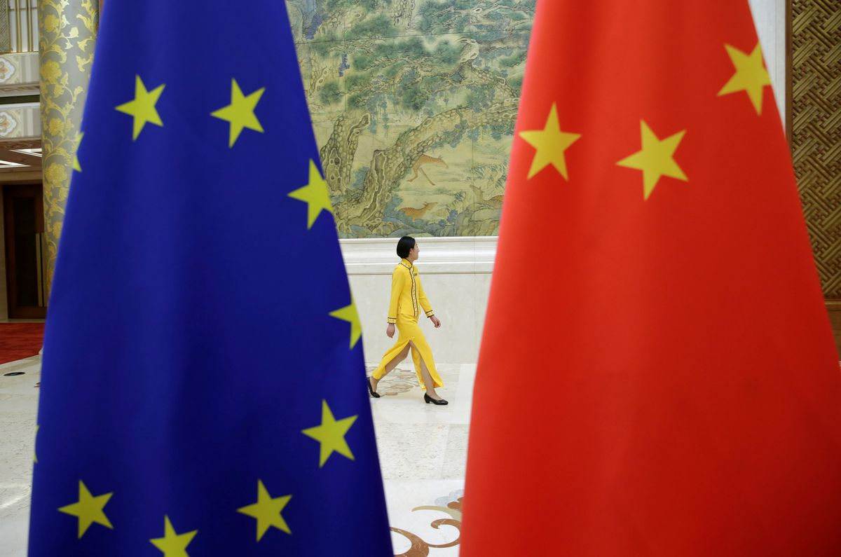 An attendant walks past EU and China flags ahead of the EU-China High-level Economic Dialogue at Diaoyutai State Guesthouse in Beijing, China June 25, 2018. Photo by Reuters/Jason Lee.