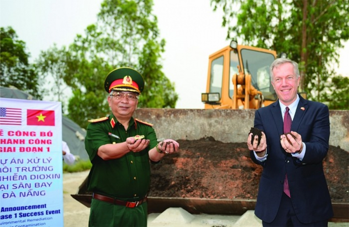 Deputy Minister of Defense Nguyen Chi Vinh and former US Ambassador to Vietnam Ted Osius holding a handful of soil that has been completely decontaminated at Da Nang Airport. (Photo: Ministry of Foreign Affairs)