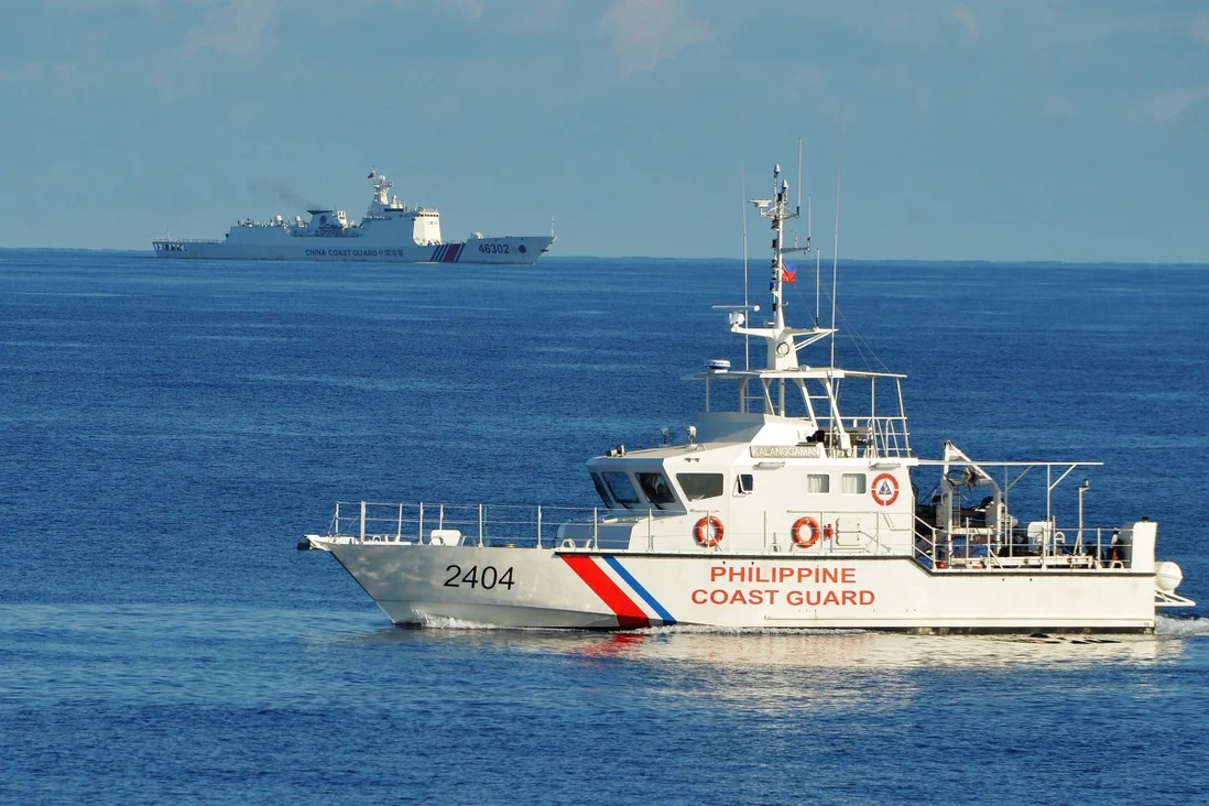 A Philippine coastguard ship and a Chinese coastguard ship pass each other near Scarborough Shoal in the South China Sea. Photo: AFP
