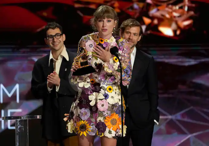 """Taylor Swift accepts the award for album of the year for """"Folklore"""" at the 63rd annual Grammy Awards in Los Angeles. In the background are her collaborators, Jack Antonoff, left, and Aaron Dessner. (Chris Pizzello/Invision/AP)"""