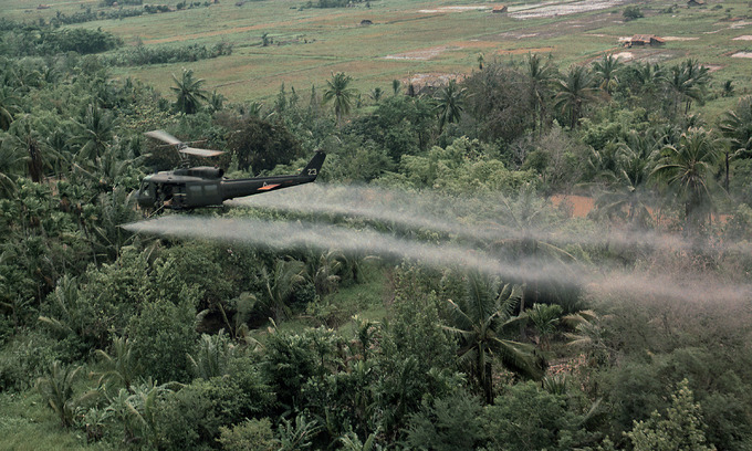 A U.S. helicopter sprays Agent Orange on a dense jungle area in the Mekong Delta during the Vietnam War. Photo by Shutterstock.
