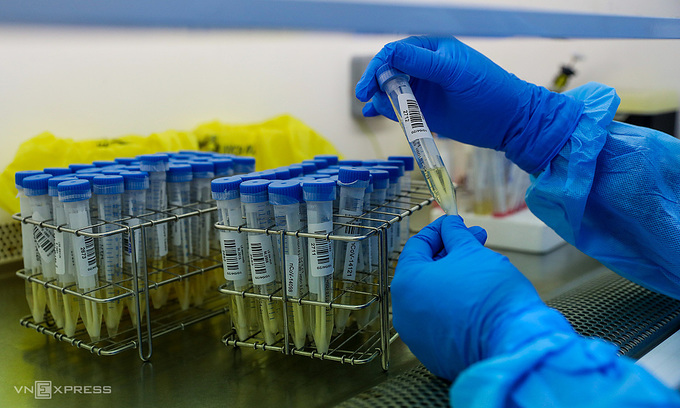 A medic holds a tube with samples taken for the new coronavirus tests at the HCMC Hospital for Tropical Diseases, March 2020. Photo by VnExpress/