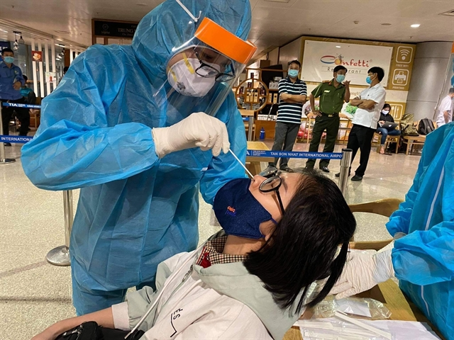 Health workers take samples for COVID-19 tests on an employee at Tân Sơn Nhất Airport on February 6. VNA/VNS Photo Đinh Hằng