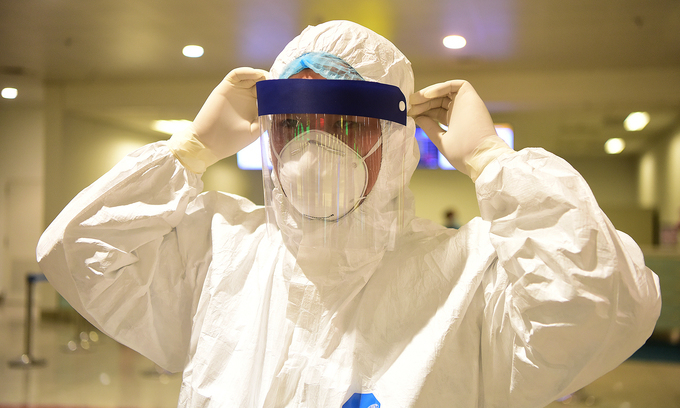 A medical worker is equipped with a medical mask, face shield and protective suit at Hanoi's Noi Bai Airport, March 18, 2020. Photo by VnExpress/Giang Huy.