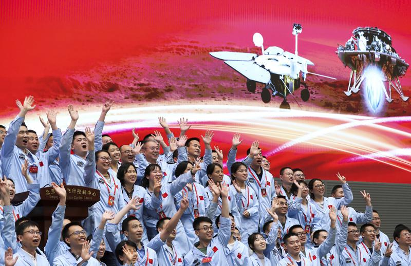 In this photo released by Xinhua News Agency, members at the Beijing Aerospace Control Center celebrate after China's Tianwen-1 probe successfully landed on Mars, at the center in Beijing, Saturday, May 15, 2021. China landed a spacecraft on Mars for the first time on Saturday, a technically challenging feat more difficult than a moon landing, in the latest advance for its ambitious goals in space. (Jin Liwang/Xinhua via AP)