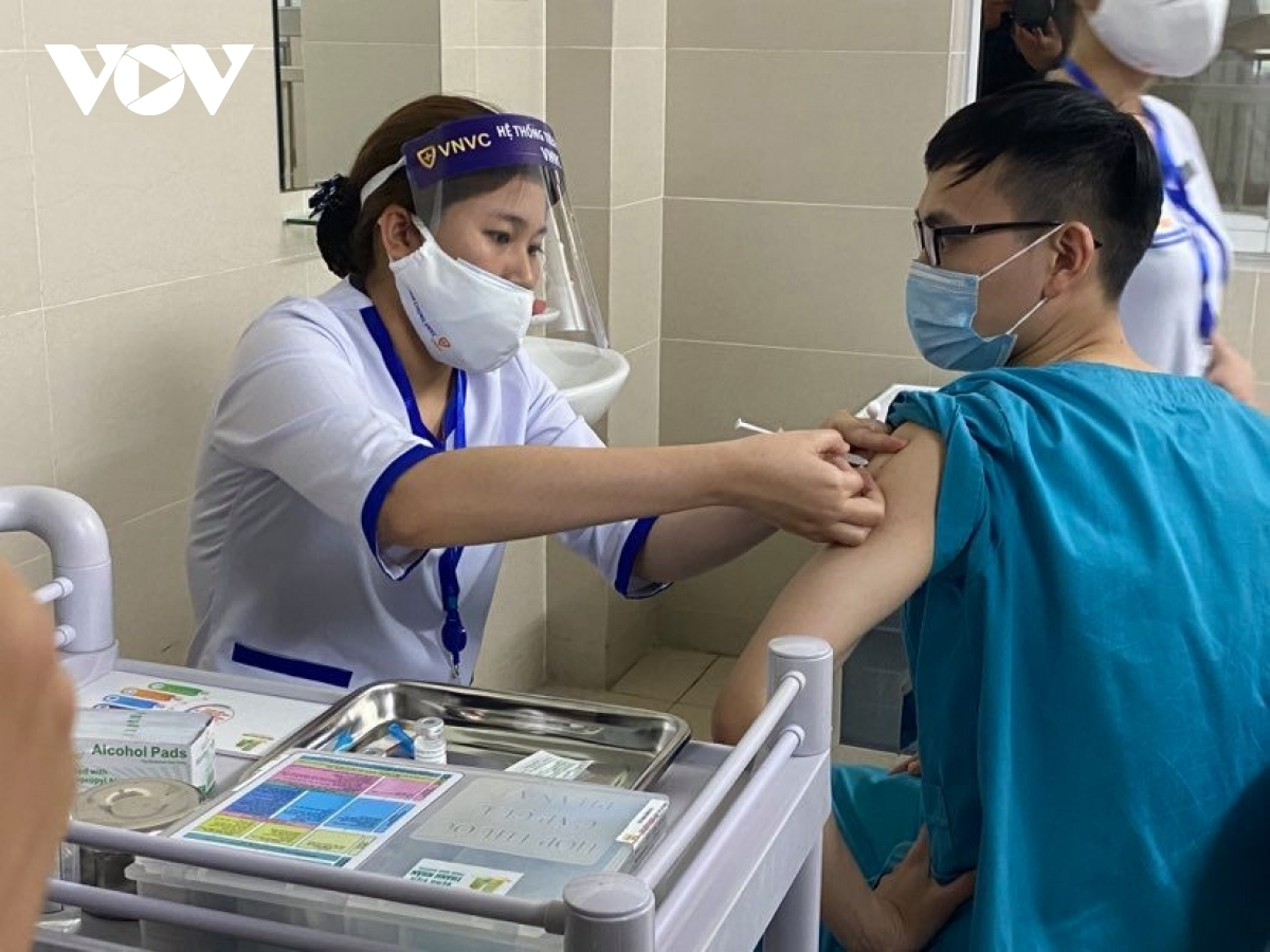 A medical worker receives a shot of AstraZeneca vaccine