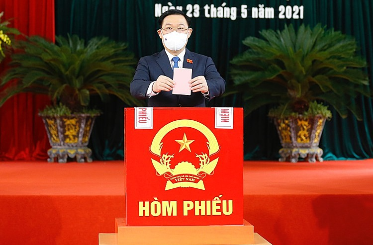 National Assembly chairman Vuong Dinh Hue casts his votes into a ballot box at a polling station in Hai Phong.