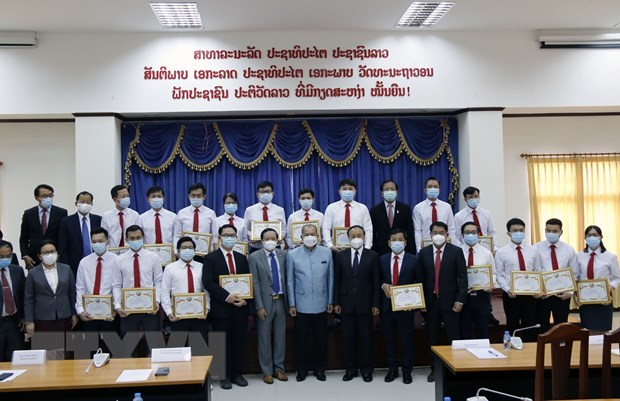 Lao Deputy Prime Minister Kikeo Khaykhamphithoune (centre) and officials pose for a group photo with Vietnamese medical experts. (Photo: VNA)
