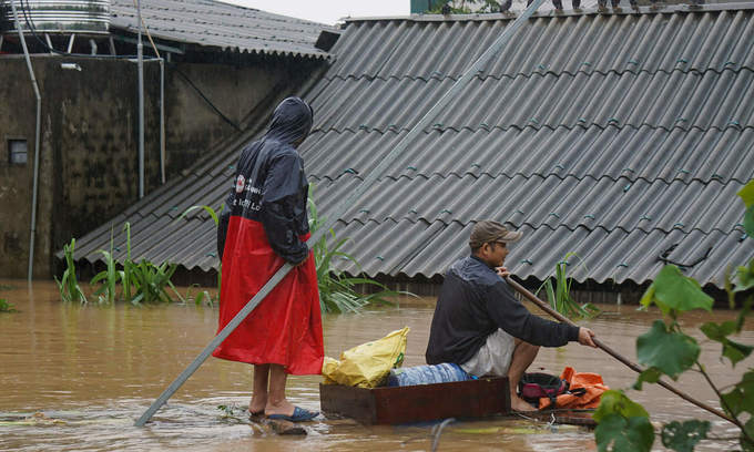 People in Ha Tinh Province travel on a raft as flood water has reached the roof of their houses, October 2020. Photo by VnExpress/Le Hoang.