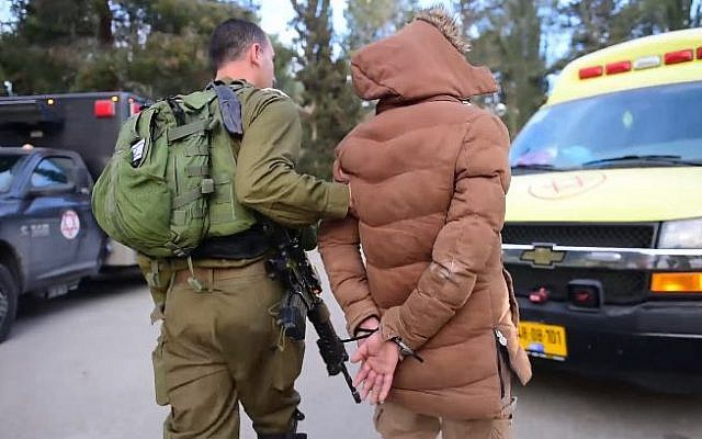 Illustrative: An Israeli soldier arresting a suspect after a raid in the West Bank city of Nablus, on March 18, 2018. (Israel Defense Forces)