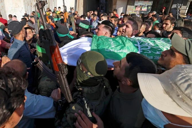 Palestinian members of Al-Qassam Brigades carry the body of one of two fighters who died after reportedly dismantling a bomb dropped in Gaza by Israeli forces, who said they arrested a Hamas leader in the West Bank. (AFP)