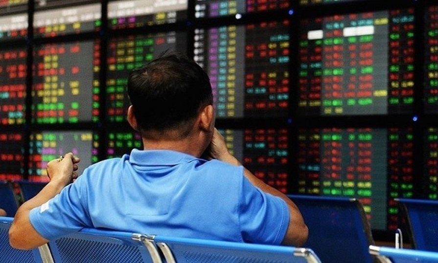 An investor watches stock prices at a brokerage office in Hanoi. Photo by AFP.