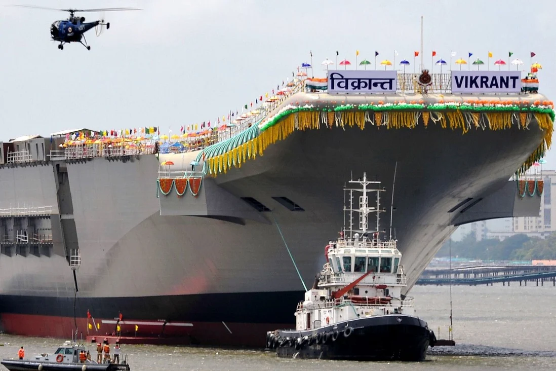 Tugboats guide India's domestically-built aircraft carrier INS Vikrant as it leaves the Cochin Shipyard after its launch ceremony in 2013. Sea trials are expected to begin next month. Photo: AFP