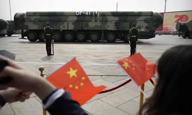 Chinese military vehicles carrying DF-41 ballistic missiles drive past flag-waving spectators during a parade in Beijing. Photograph: AP