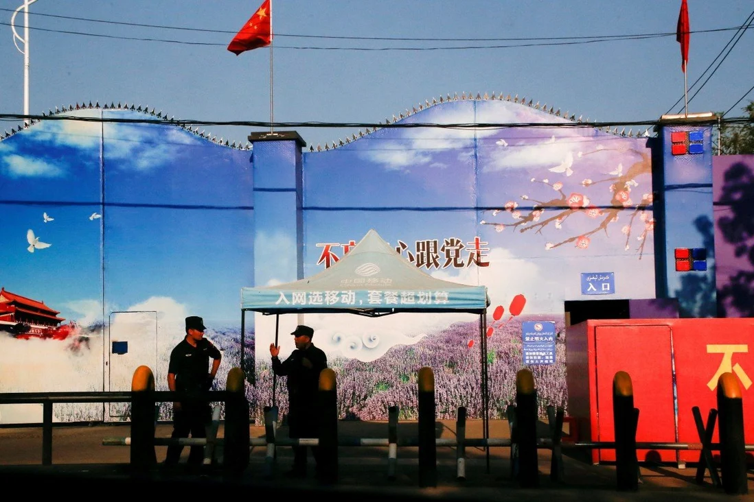 """Security guards stand at the gates of what is officially called a """"vocational skills education centre"""" in Xinjiang. Photo: Reuters"""